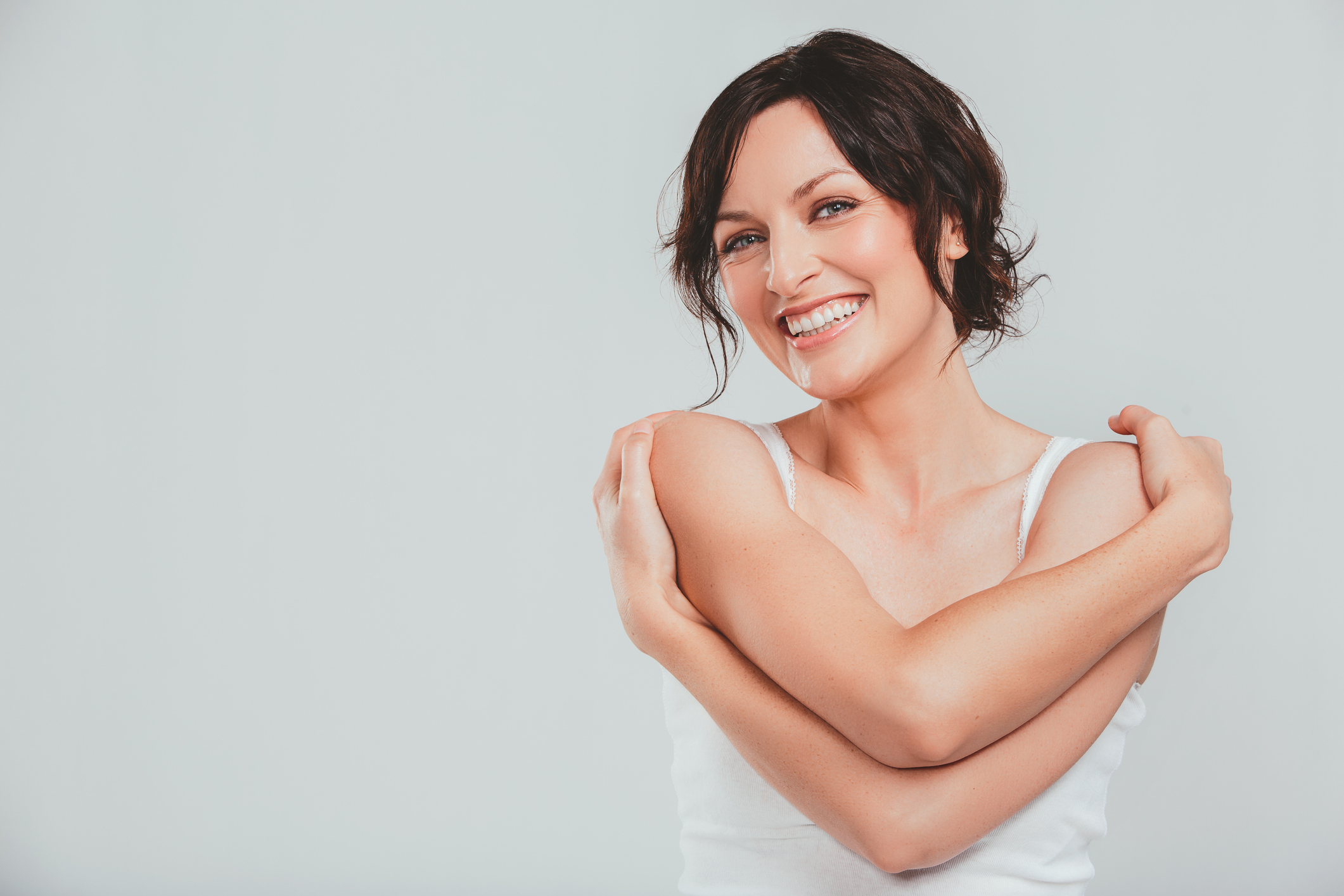 Woman hugging herself while smiling